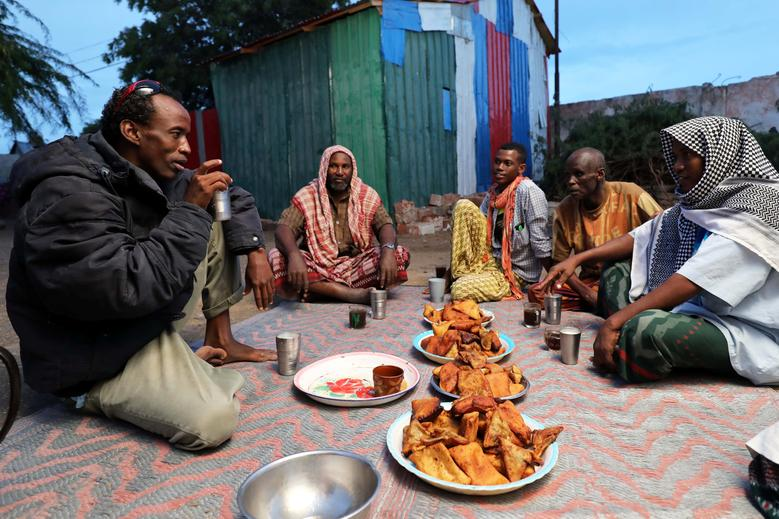 Internally displaced Somali Muslim men eat Iftar meals at a makeshift camp in Mogadishu, Somalia, May 7. REUTERS/Feisal Omar