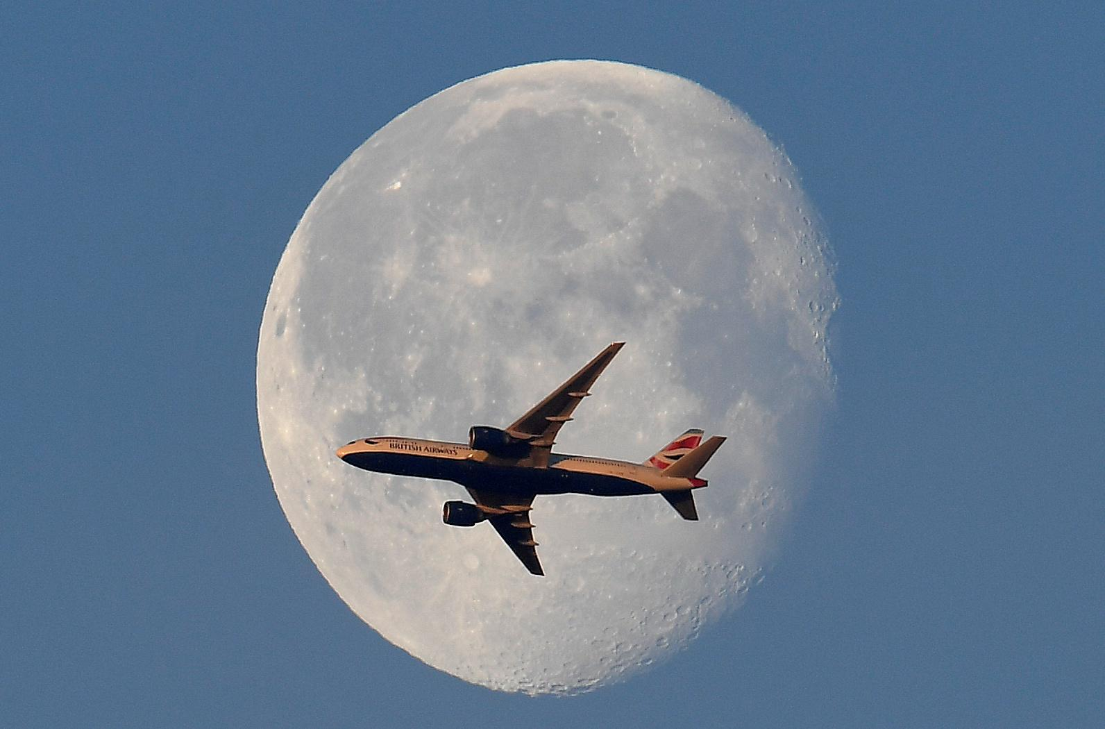 A British Airways passenger plane flies in front of the moon above London, Britain, May 3, 2018. Toby Melville