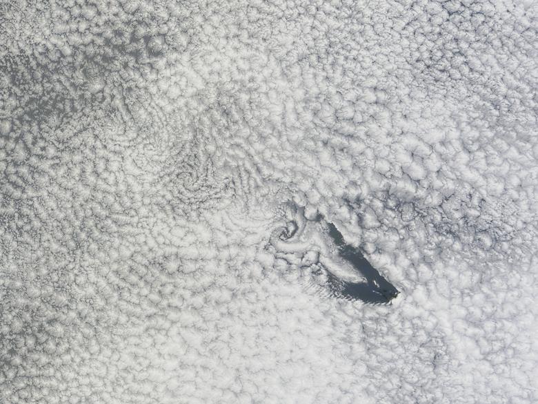 Una imagen en color verdadero de la isla de Santa Elena y una banda de vórtices de nubes arrastradas por el viento que se arrastran hacia el lado de sotavento de la isla sobre el Océano Atlántico Sur. REUTERS / NASA