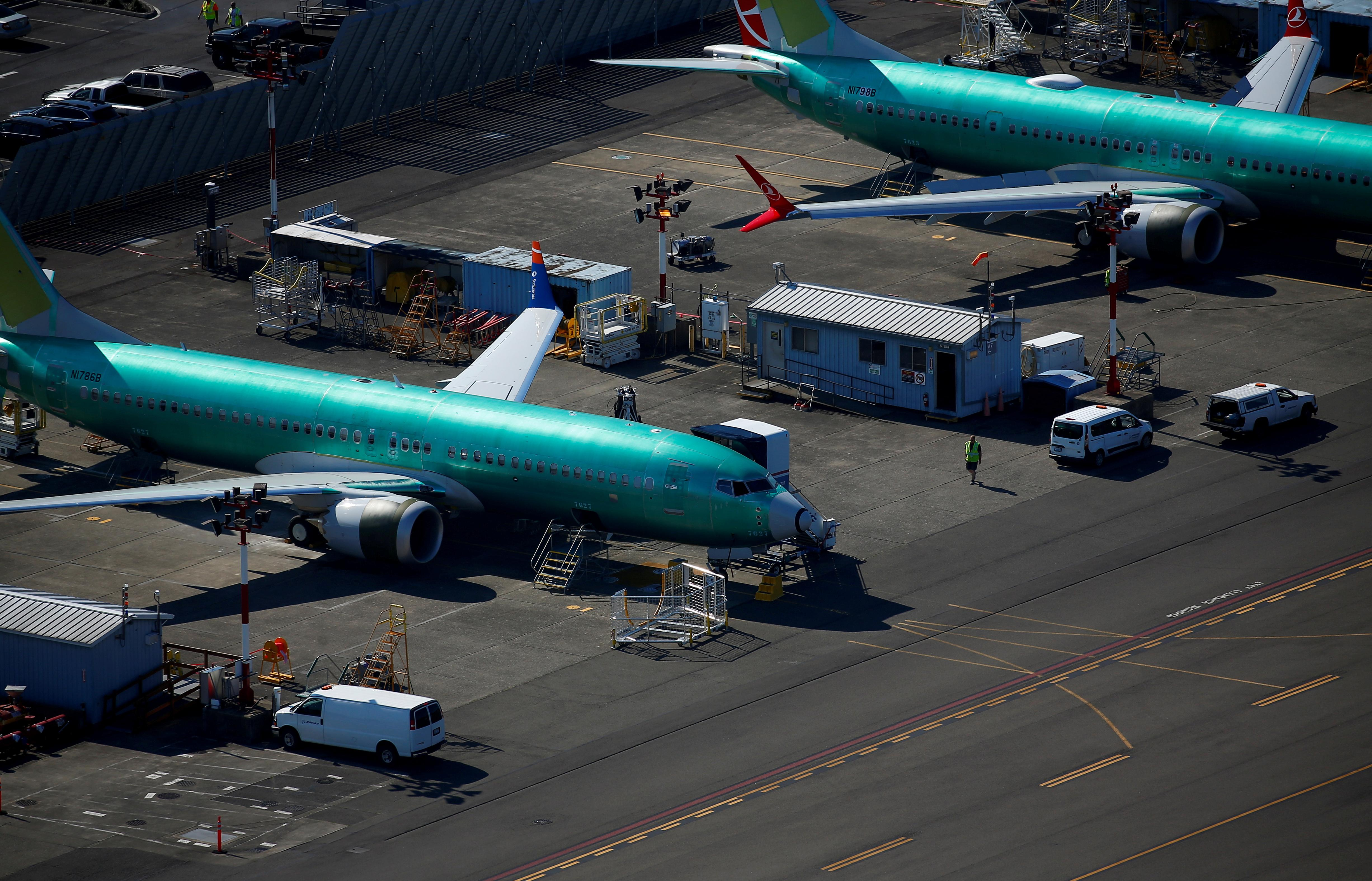 A worker walks past unpainted Boeing 737 MAX aircraft seen parked in an aerial photo at Renton Municipal Airport near the Boeing Renton facility in Renton, Washington, U.S. July 1, 2019. Lindsey Wasson