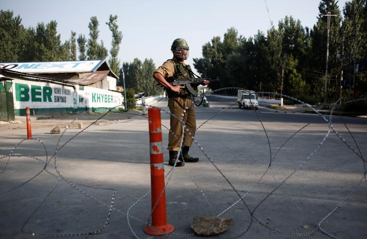 An Indian security personnel stands guard on a deserted road during...