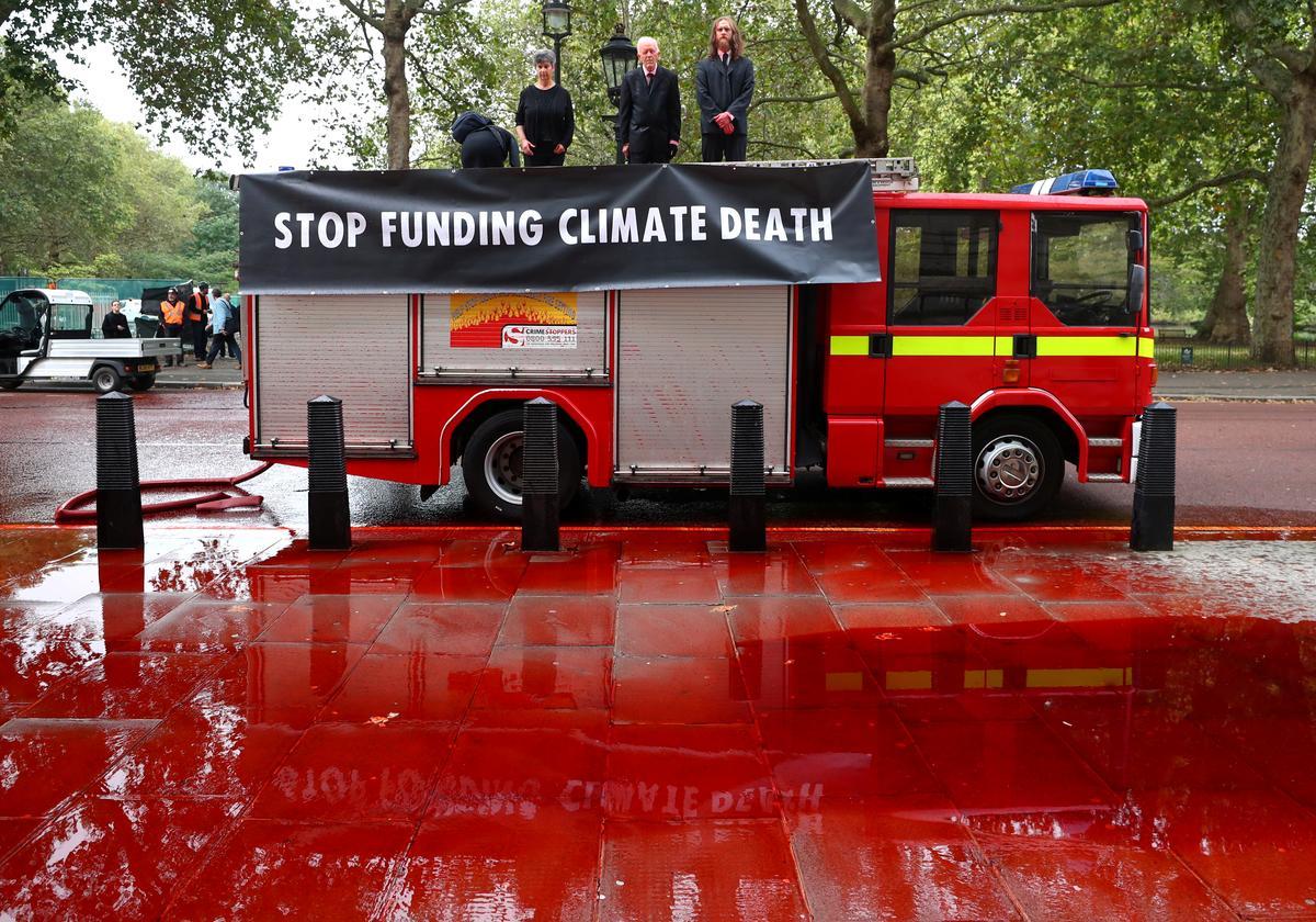 Aktiviste vir klimaatsverandering spuit rooi verf by die Britse tesourie uit 'n brandweerwa