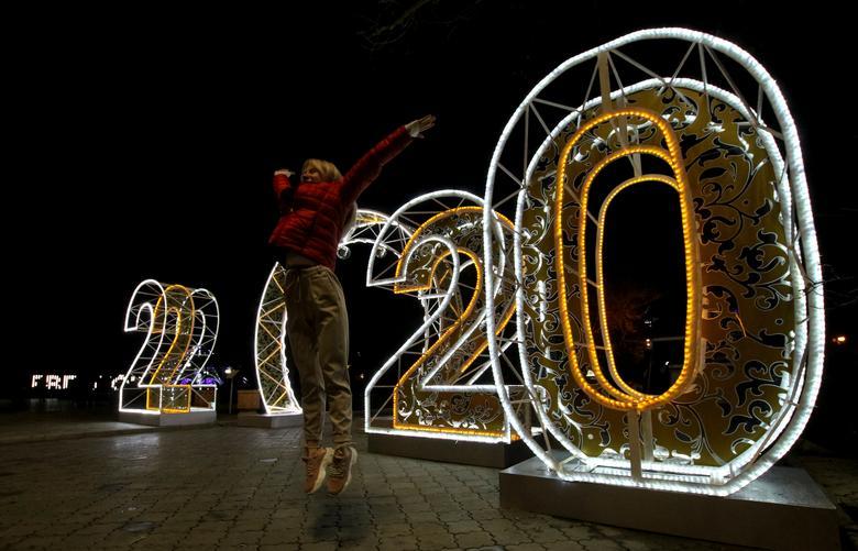 Una mujer salta para una foto frente a las luces festivas para el próximo año nuevo en Yevpatoriya, Crimea, 22 de diciembre de 2019. REUTERS / Alexey Pavlishak