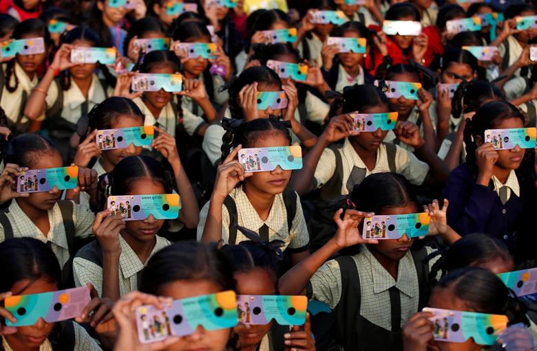 Los niños usan visores solares para ver un eclipse solar anular en Ahmedabad, India, 26 de diciembre de 2019. REUTERS / Amit Dave