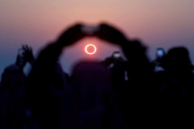 Las personas toman fotos con sus teléfonos inteligentes mientras monitorean el eclipse solar anular en Jabal Arba (Cuatro Montañas) en Hofuf, en la Provincia Oriental de Arabia Saudita, 26 de diciembre de 2019. REUTERS / Hamad I Mohammed