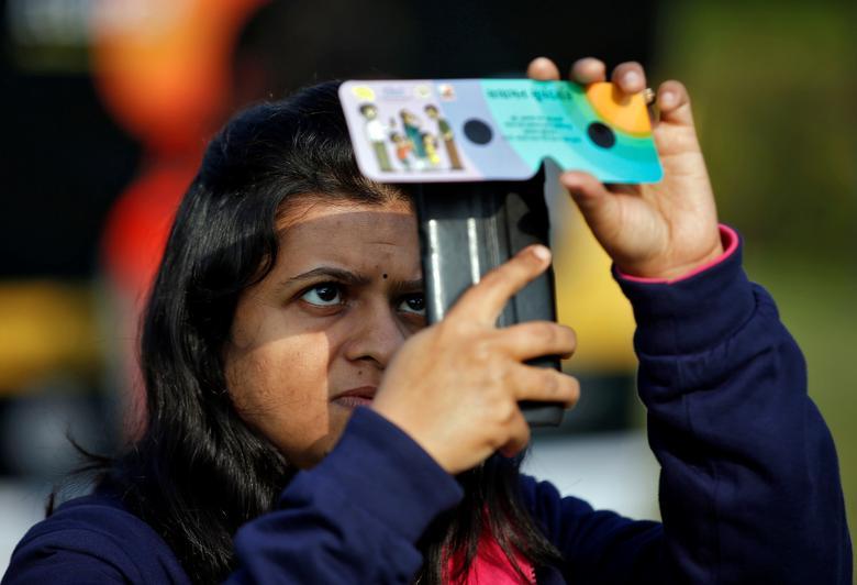 Una mujer usa su teléfono móvil y visores solares para tomar fotografías del eclipse solar anular en Ahmedabad, India, 26 de diciembre de 2019. REUTERS / Amit Dave
