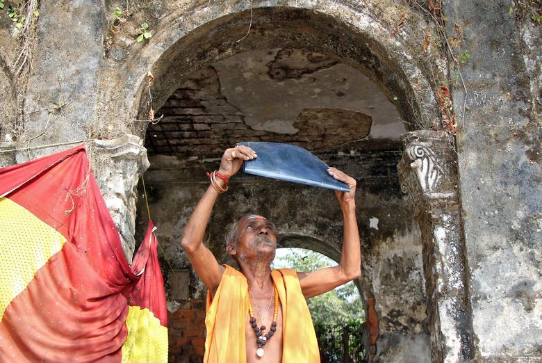 Un sacerdote hindú observa un eclipse solar parcial a través de una película de rayos X expuesta fuera de un templo en Agartala, India, 26 de diciembre de 2019. REUTERS / Jayanta Dey