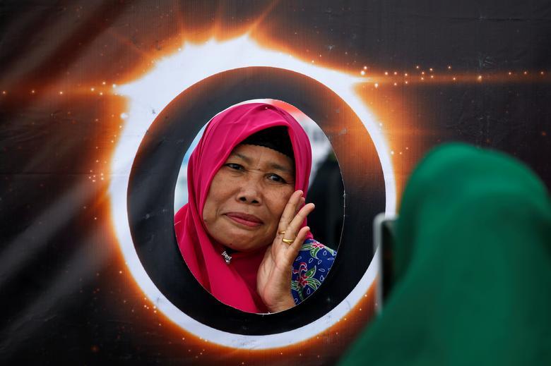 Una mujer posa para fotos detrás de una pancarta que representa el eclipse solar durante el eclipse solar anular en Siak, provincia de Riau, Indonesia, 26 de diciembre de 2019. REUTERS / Willy Kurniawan