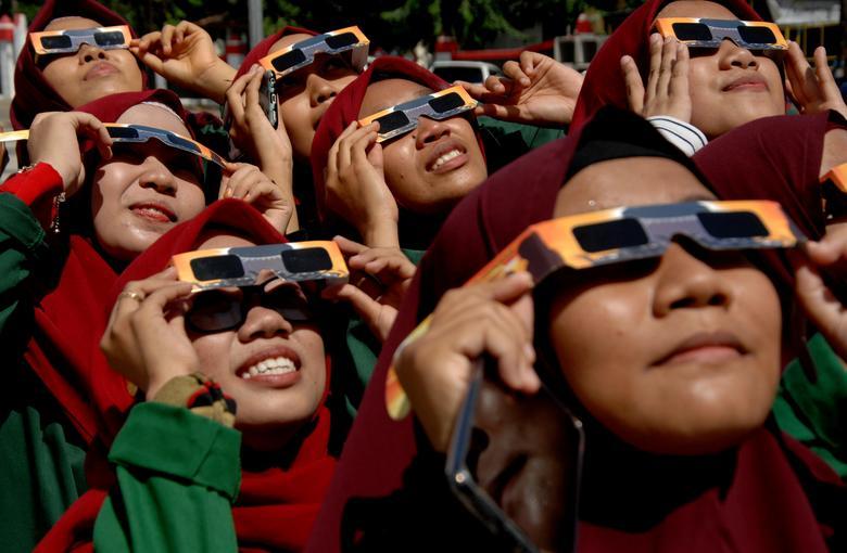 Las mujeres que usan anteojos protectores especiales observan el eclipse solar anular en la mezquita de Gowa, South Sulawesi, Indonesia, 26 de diciembre de 2019. Antara Foto / Abriawan Abhe / via REUTERS