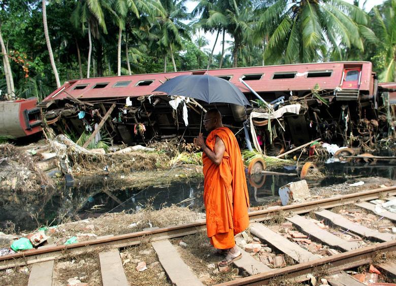 Un monje budista mira un vagón destrozado después de que un tren entero fue destruido en Paraliya, Sri Lanka, el 30 de diciembre de 2004. REUTERS / Kieran Doherty
