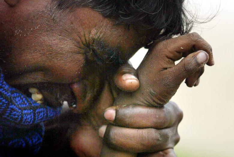 Un hombre indio llora mientras sostiene la mano de su hijo de ocho años asesinado en un tsunami en Cuddalore, India, el 27 de diciembre de 2004. REUTERS / Arko Datta