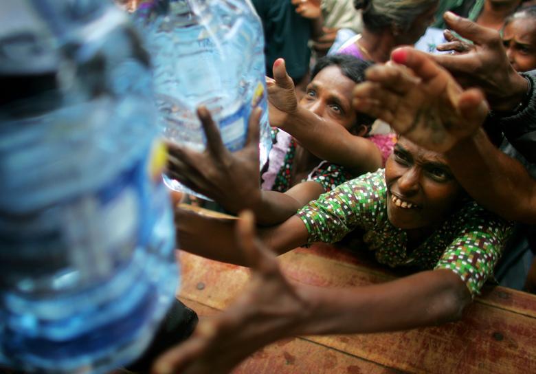 Los sobrevivientes del tsunami se apresuran a buscar agua mientras los descargan de un camión de ayuda en Karaitivu, en la costa este de Sri Lanka, el 2 de enero de 2005. REUTERS / Kieran Doherty