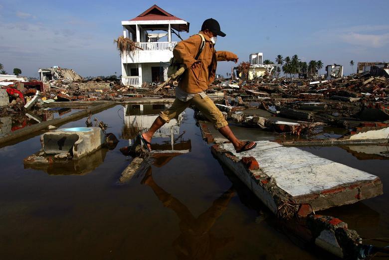 Un hombre de Acehnese salta sobre un charco de agua cerca de las ruinas de su casa en la ciudad de Banda Aceh, azotada por el tsunami, en la isla indonesia de Sumatra, el 8 de enero de 2005. REUTERS / Beawiharta