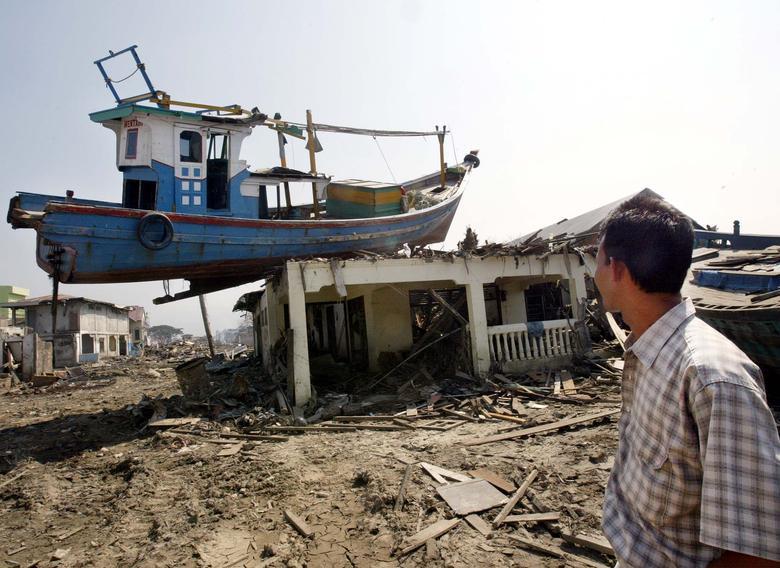 Un hombre de Acehnese mira un bote abandonado en la parte superior de una casa como resultado del tsunami en la ciudad de Banda Aceh, provincia de Indonesia, el 24 de febrero de 2005. REUTERS / Supri Supri