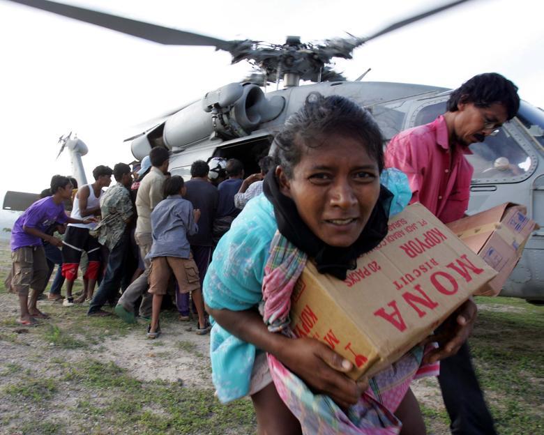Los refugiados del tsunami reciben suministros distribuidos por el grupo de ataque del portaaviones USS Abraham Lincoln en Krueng Raya, al noreste de Banda Aceh, Indonesia, el 3 de enero de 2005. REUTERS / Yuriko Nakao