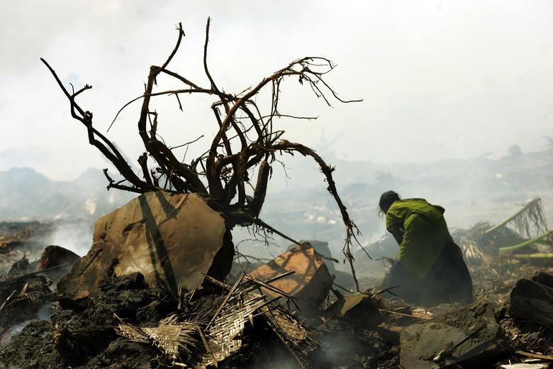 Una sobreviviente india del tsunami busca sus pertenencias entre los escombros de su casa destruida por el tsunami que está siendo quemada por trabajadores indios en una aldea de pescadores en Nagapattinam, India, 3 de enero de 2005. REUTERS / Arko Datta