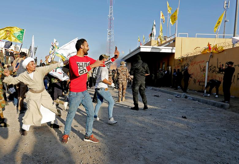 Protesters and militia fighters throw stones towards the U.S. Embassy during a protest to condemn air strikes on bases belonging to Hashd al-Shaabi (paramilitary forces), in Baghdad, Iraq December 31, 2019. REUTERS/Wissm al-Okili