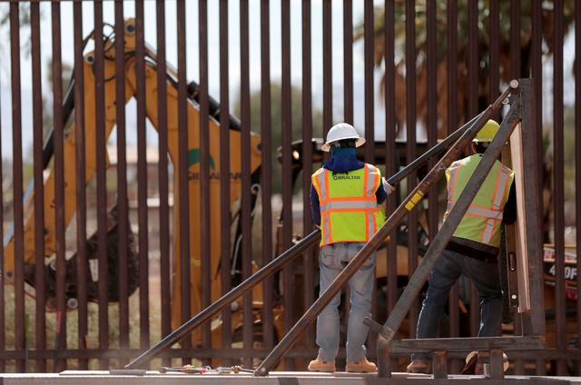 FILE PHOTO: Construction workers raise the 30-foot high bollard style wall, at the US-Mexico border to replace a section of the border wall near Calexico, California, U.S., February 23, 2018. REUTERS/Earnie Grafton