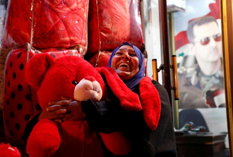 Una mujer reacciona mientras sostiene un oso de peluche rojo a la venta para el Día de San Valentín en Damasco, Siria.  REUTERS / Yamam Al Shaar