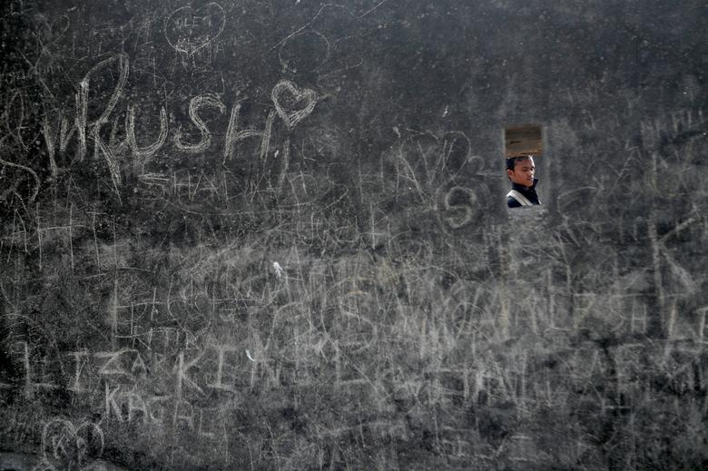 Un hombre camina junto a un fuerte muro cubierto de graffiti en el Día de San Valentín en Mumbai, India.  REUTERS / Francis Mascarenhas