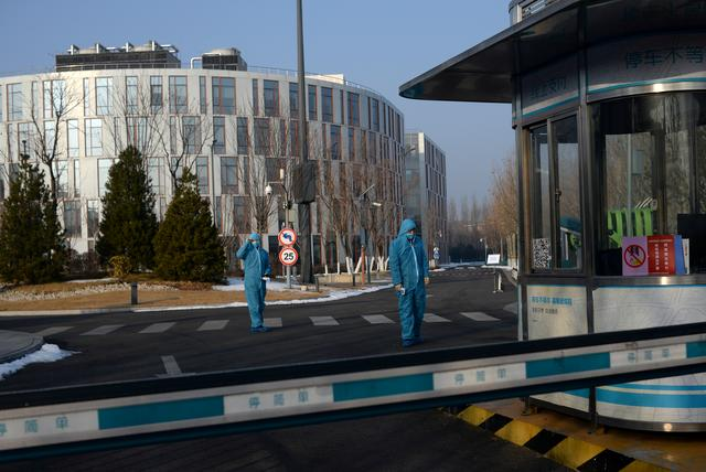 FILE PHOTO: Security guards wearing protective suits and face masks hold thermometers as they stand at the entrance to the China Transinfo Technology Co, in the morning after the extended Lunar New Year holiday caused by the novel coronavirus outbreak, in Zhongguancun Software Park, in Beijing, China February 10, 2020. REUTERS/Tingshu Wang/File Photo