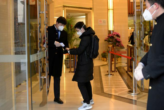 REFILED PHOTO: Jin Yang, 28, has his temperature checked at an entrance to his office, in the morning on his first day of returning to work after the extended Lunar New Year holiday caused by the novel coronavirus outbreak, in Beijing, China February 10, 2020. REUTERS/Tingshu Wang/File Photo