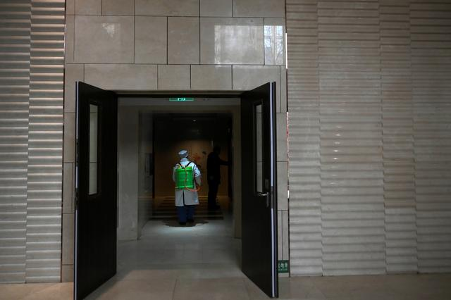 Worker Wang Fu wearing a face mask sprays disinfectant at an apartment of a residential compound, as the country is hit by an outbreak of the novel coronavirus, in Beijing, China February 21, 2020. REUTERS/Tingshu Wang