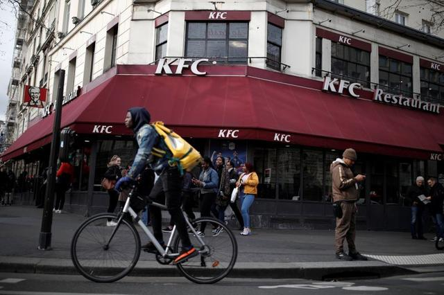 A man cycles past the Strasbourg Saint-Denis branch of the chicken chain KFC where a commemorative plaque on the self-ordering kiosk used by celebrity couple?Kim Kardashian?and?Kanye West?was installed by the branch in Paris, France, February 21, 2020. REUTERS/Benoit Tessier