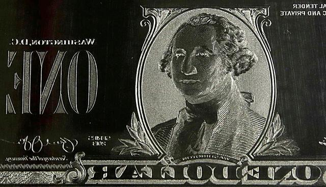 FILE PHOTO: The image of United States President George Washington is seen on an engraving plate for a US one dollar bill at the Bureau of Engraving and Printing in Washington November 14, 2014. The plate goes on the printing press which prints the currency. REUTERS/Gary Cameron