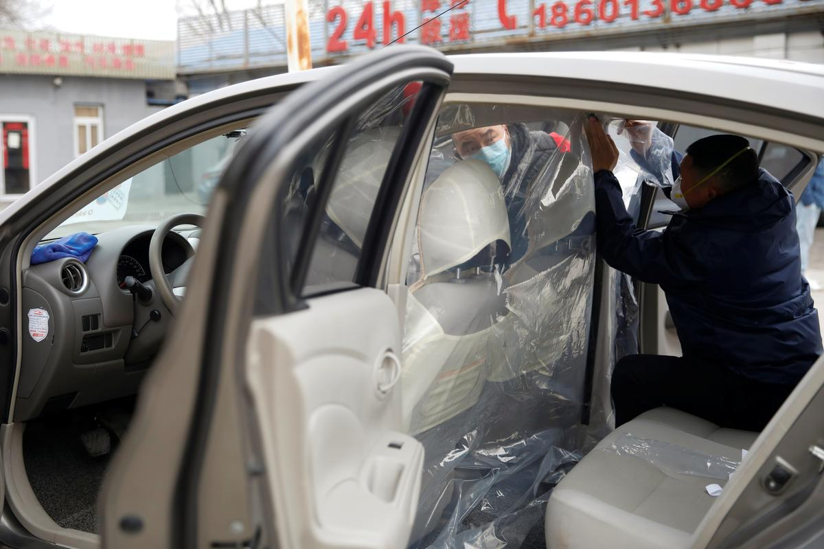 Amid virus, Chinese ride-sharing cars install added layer of protection