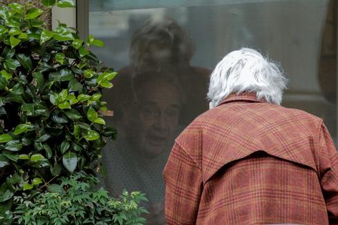 Love speaks through glass panes at coronavirus facility