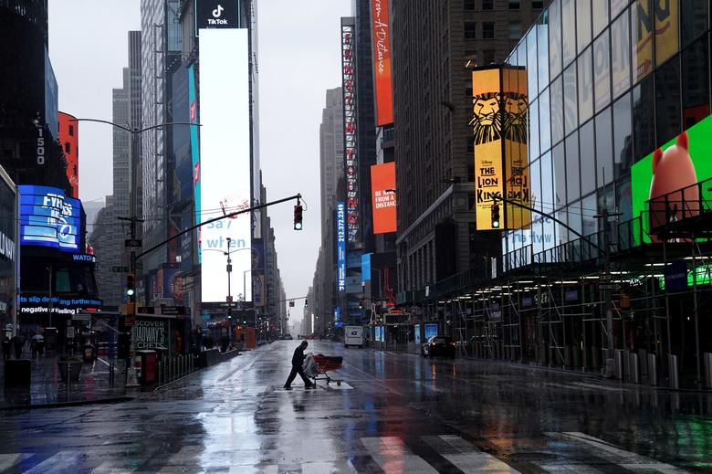 A homeless person pushes his belongings through a deserted Times Square in Manhattan, New York, March 23, 2020. REUTERS/Carlo Allegri