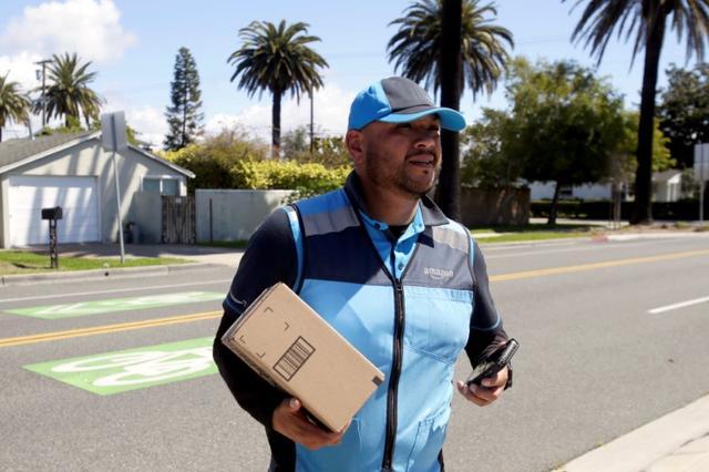 Joseph Alvarado makes a delivery for Amazon during the outbreak of the coronavirus disease (COVID-19) in Costa Mesa, California, U.S., March 23, 2020.      REUTERS/Alex Gallardo