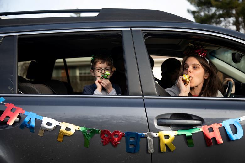 Дана Баер и ее сын Джейкоб Баер желают Эвери Слуцкому счастливого шестилетия от их автомобиля во время празднования дня рождения вождения, поскольку они поддерживают социальную дистанцию в Уэст-Блумфилде, штат Мичиган, 24 марта 2020 года. РЕЙТЕР / Эмили Элконин