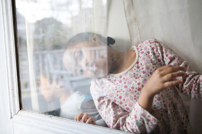 Дочь и племянник Джой Мэлоун смотрят в окно своего дома на пустынную улицу в Нью-Рошель, Нью-Йорк, 20 марта 2020 года. РЕЙТЕР / Джой Мэлоун