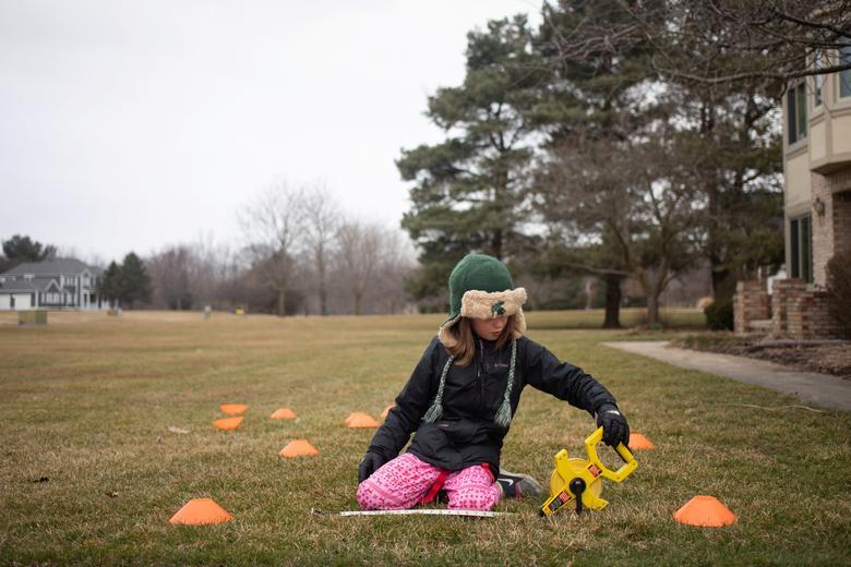8-летняя Молли Магуайр измеряет расстояние между шишками во время упражнения по математике, изучая, как рассчитать площадь различных форм на ее переднем дворе, так как школы закрыты в Салеме, штат Мичиган, 24 марта 2020 года. REUTERS / Emily Elconin