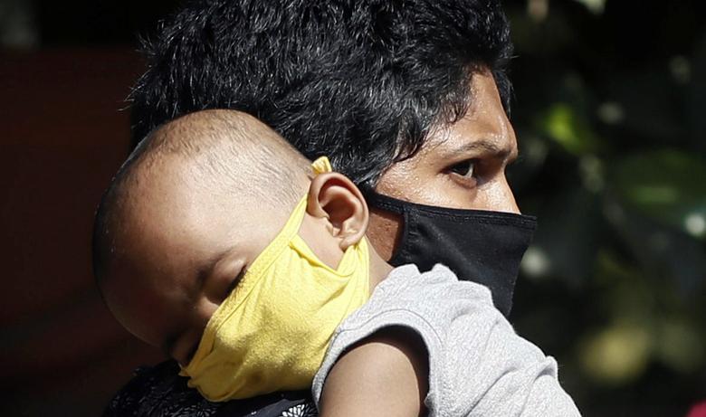 Человек несет ребенка в помещении больницы, в Мумбаи, Индия, 17 марта 2020 года. REUTERS / Francis Mascarenhas