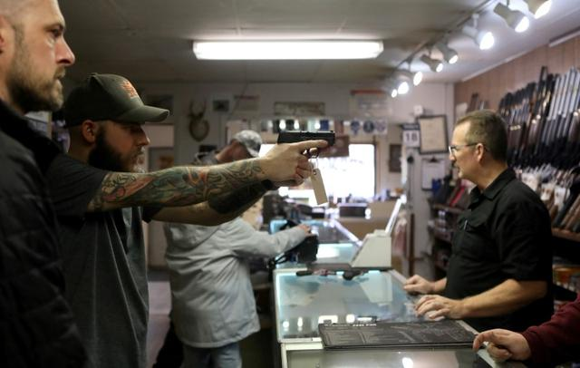 FILE PHOTO: A man holds a semi-automatic handgun at Frontier Arms & Supply gun shop amid fears of the global growth of coronavirus disease (COVID-19) cases, in Cheyenne, Wyoming, U.S. March 18, 2020.  REUTERS/Jim Urquhart/File Photo