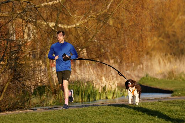 A man and his dog on a run, as the spread of the coronavirus disease (COVID-19) continues, High Wycombe, Britain, March 26, 2020. REUTERS/Eddie Keogh