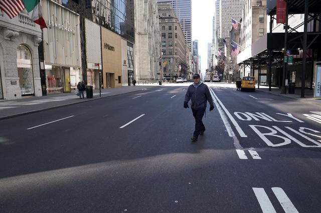 FILE PHOTO: A lone man crosses 5th Ave following the outbreak of coronavirus disease (COVID-19), in the Manhattan borough of New York City, New York, U.S., March 24, 2020. REUTERS/Carlo Allegri/