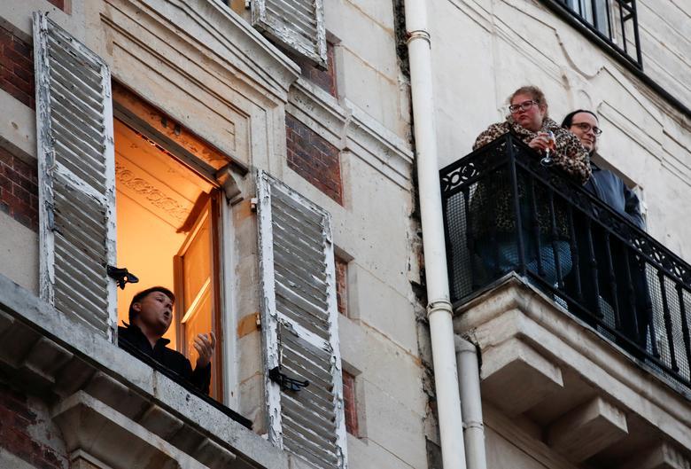 Французький тенор Стефан Сенечаль співає з вікна своєї квартири в Парижі, Франція, 24 березня 2020 року. REUTERS / Gonzalo Fuentes