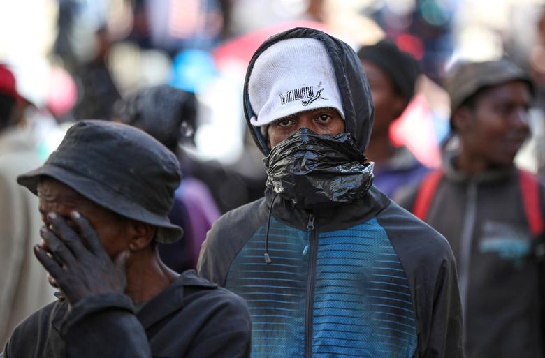 Um homem sem-teto cobre seu rosto com plástico enquanto espera para ser transportado para um abrigo para sem-teto em Joanesburgo, África do Sul, em 27 de março de 2020. REUTERS / Siphiwe Sibeko