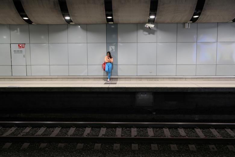 Um viajante solitário fica na plataforma de uma estação de trem deserta durante a hora do rush da manhã em Sydney, Austrália, 24 de março de 2020. REUTERS / Loren Elliott