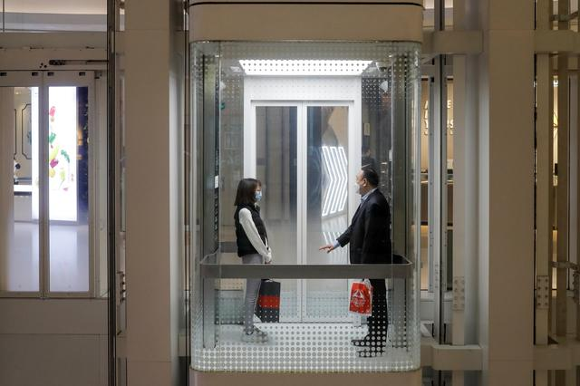 People observe social distancing as they share a lift in a department store in Beijing following an outbreak of the novel coronavirus disease (COVID-19), China, March 25, 2020. Picture taken March 25, 2020.  REUTERS/Thomas Peter