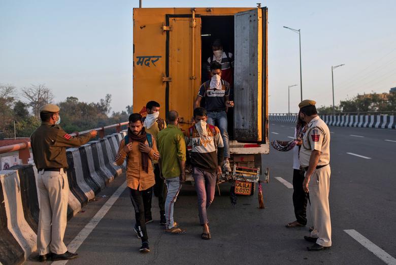 Trabalhadores migrantes saem de um caminhão refrigerado após serem parados pela polícia enquanto tentam retornar às suas aldeias em Nova Délhi, na Índia, em 30 de março de 2020. REUTERS / Danish Siddiqui