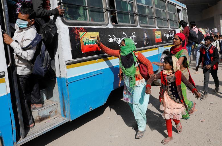 Uma trabalhadora migrante segura a mão da filha enquanto tenta embarcar em um ônibus lotado para retornar à sua aldeia em Ghaziabad, nos arredores de Nova Délhi, na Índia, em 29 de março de 2020. REUTERS / Adnan Abidi