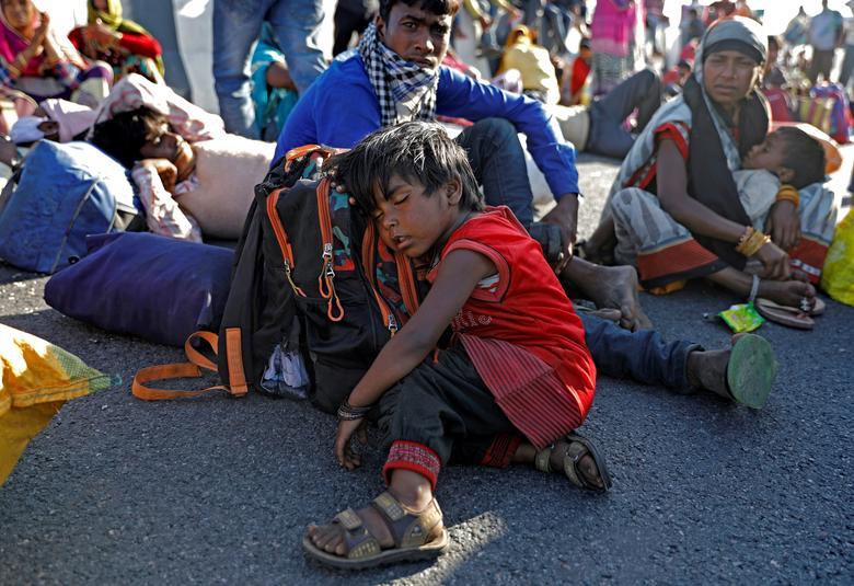 A filha de um trabalhador migrante dorme em uma rodovia quando eles não conseguiram um ônibus para retornar à sua aldeia em Nova Délhi, na Índia, em 29 de março de 2020. REUTERS / Adnan Abidi