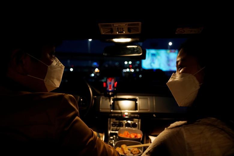 Um casal se prepara para assistir a um filme de seu carro em um cinema drive-in temporariamente criado para residentes, mantendo o distanciamento social após o surto da doença por coronavírus, em Seul, Coréia do Sul, em 27 de março de 2020. REUTERS / Kim Hong -Ji