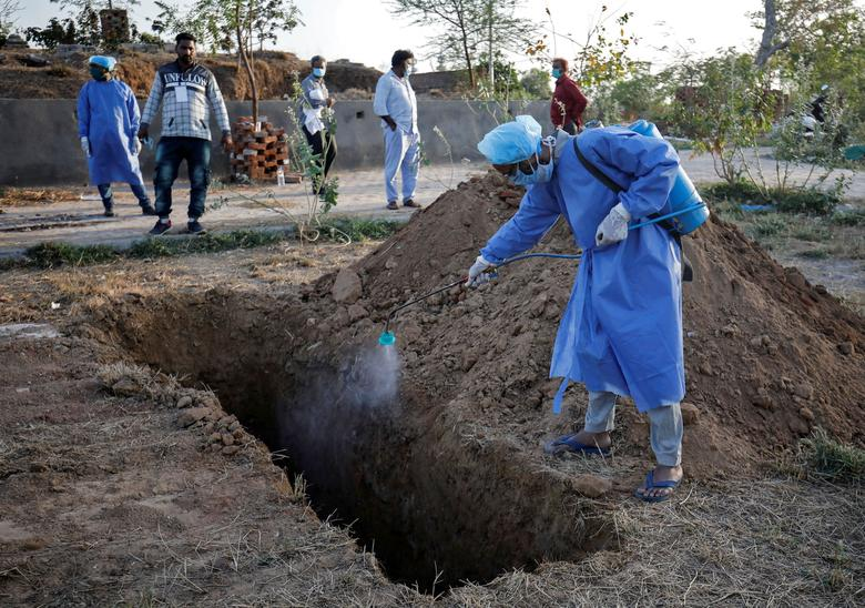 Муниципальный служащий в защитном костюме распыляет дезинфицирующий раствор в могиле перед похороной женщины, которая умерла от COVID-19 в Ахмедабаде, Индия, 28 марта 2020 года. REUTERS / Amit Dave
