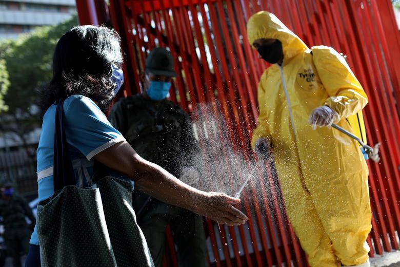 Робочий дезінфікує руки клієнта на вході в громадський ринок в Каракасі, Венесуела, 18 березня. REUTERS / Manaure Quintero